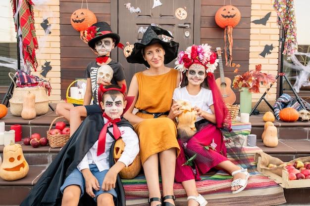 Giovane donna felice in cappello della strega e vestito giallo che si siede sulla scala dalla porta decorata della casa tra i bambini di halloween in costumi intelligenti