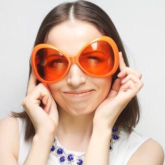 Giovane donna felice con grandi occhiali da sole arancioni, pronta per la festa
