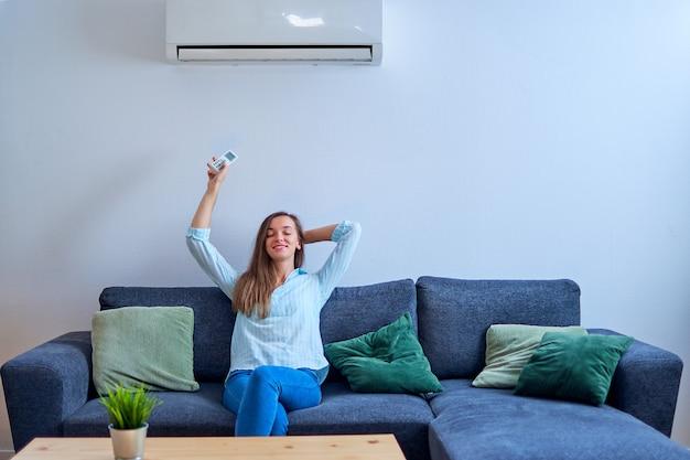 Giovane donna felice con gli occhi chiusi, seduto sul divano sotto aria condizionata e regolazione della temperatura confortevole con telecomando a casa moderna