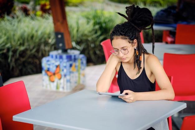 Giovane donna felice con i dreadlocks che legge dal suo tablet mentre è seduto a un tavolo 3