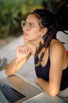 Giovane donna felice con i dreadlocks leggendo dal suo tablet mentre era seduto a un tavolo, sorridendo e pensando a qualcosa