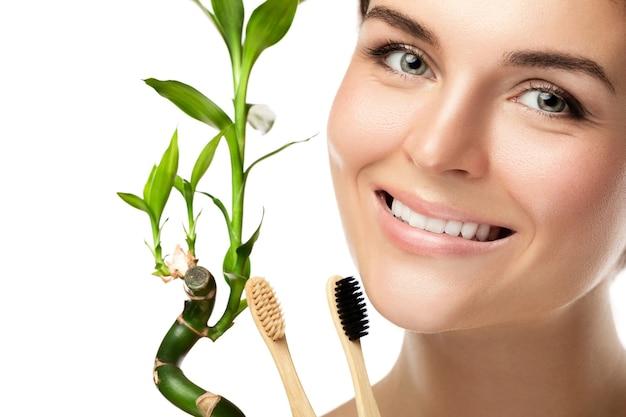 Giovane donna felice con spazzolini da denti di bambù ecologici
