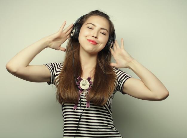 Giovane donna felice con le cuffie che ascolta musica su sfondo grigio