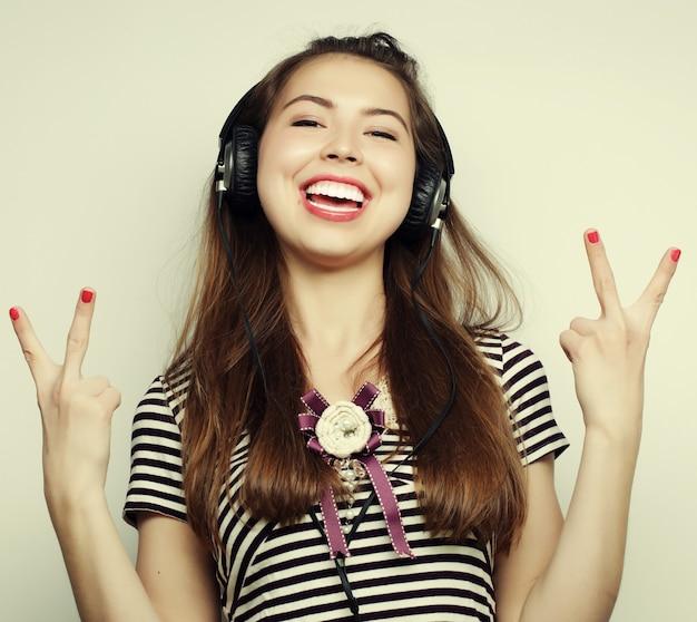 Giovane donna felice con le cuffie che ascolta musica su sfondo grigio Foto Premium