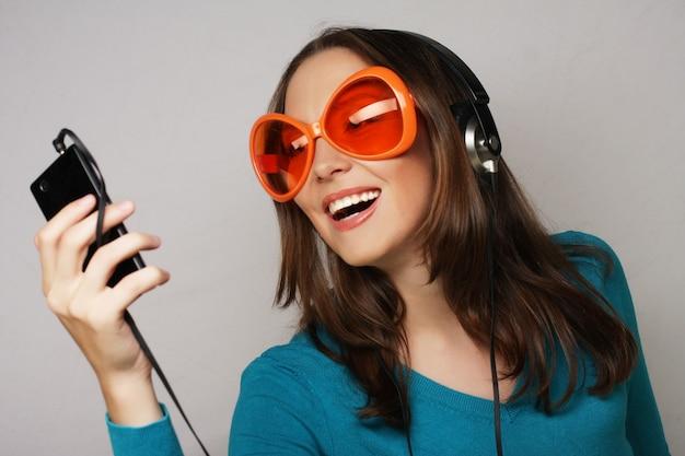 Giovane donna felice con le cuffie che ascolta musica su sfondo bianco