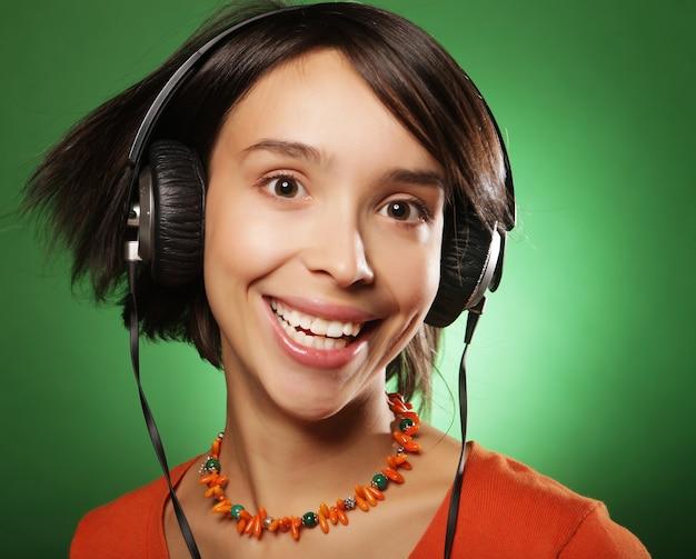 Giovane donna felice con le cuffie che ascolta musica Foto Premium