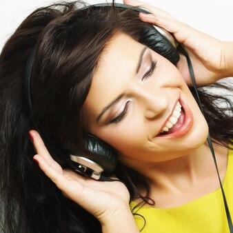 Giovane donna felice con le cuffie che ascolta musica