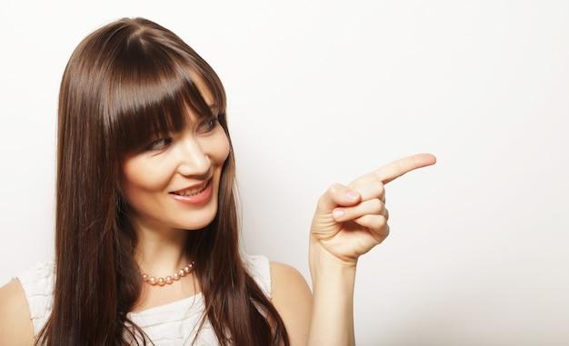 Giovane donna felice con il dito in su