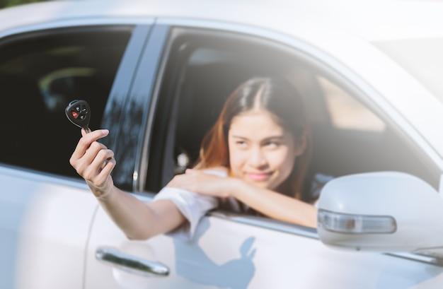 Giovane donna felice con le chiavi in mano.