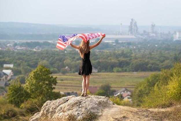 Giovane donna felice con i capelli lunghi che si alzano sventolando la bandiera nazionale americana del vento nelle sue mani in piedi su un'alta collina rocciosa godendosi la calda giornata estiva.