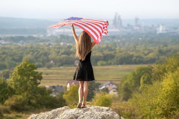 Giovane donna felice con i capelli lunghi che si alzano sventolando la bandiera nazionale americana del vento
