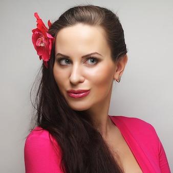 Giovane donna felice con fiore rosa nei capelli