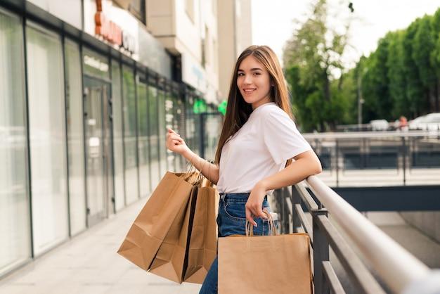Giovane donna felice con le borse della spesa camminando sulla strada del negozio.