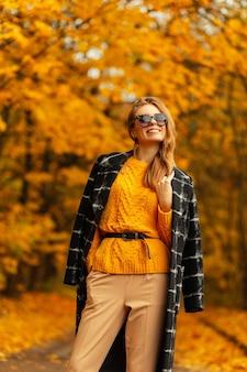 La giovane donna felice con il sorriso in vestiti di modo di autunno con gode sul fondo giallo del parco dell'acero di caduta. emozioni divertenti femminili