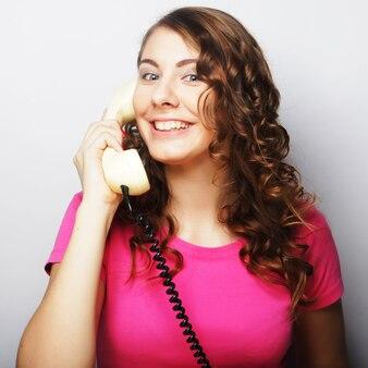 Giovane donna felice con telefono vintage, foto in studio