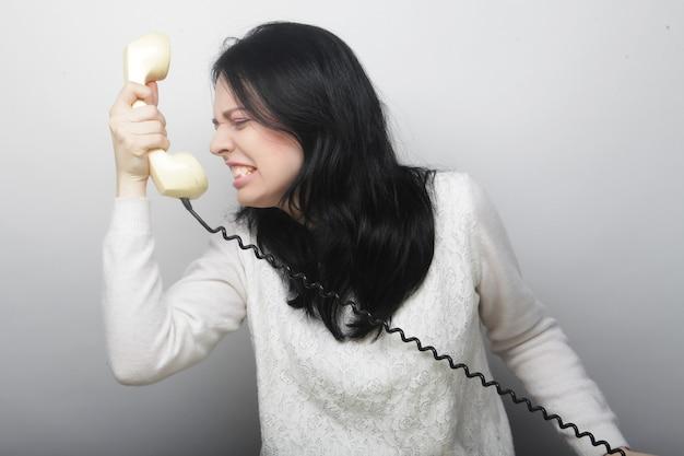 Giovane donna felice con telefono vintage