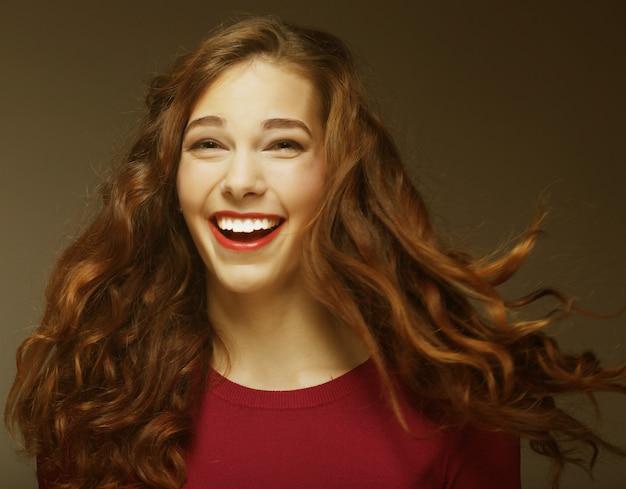 Giovane donna felice con il vento nei capelli. colpo dello studio.