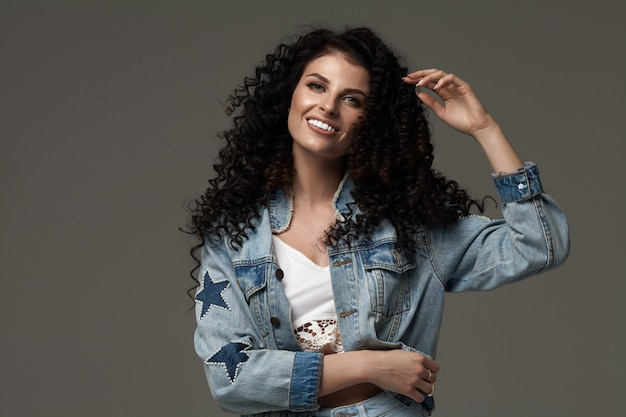Giovane donna felice con vento nei capelli. colpo dello studio
