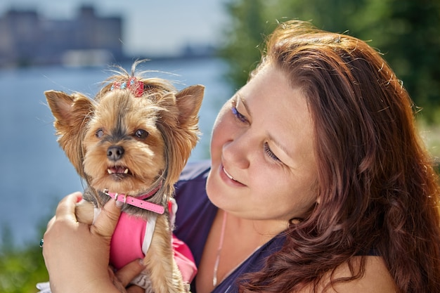 La giovane donna felice con lo yorkshire terrier in vestito rosa e collare sta camminando are