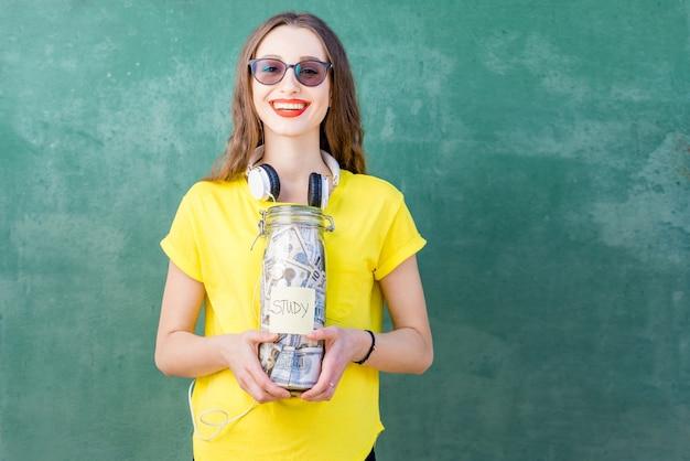 Giovane e donna felice in maglietta gialla che tiene una bottiglia con risparmi di denaro per lo studio