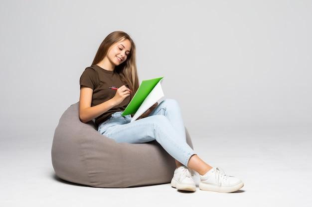 Giovane donna felice che fa alcune note nel blocco note, isolato sul muro bianco