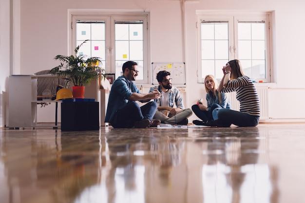 Giovani laboriosi imprenditori creativi seduti sul pavimento dell'ufficio nel cerchio e facendo insieme un business plan. il lavoro di squadra e il concetto di solidarietà.