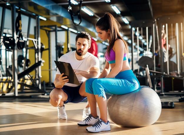 Giovane donna attiva in buona salute che si siede sulla palla della palestra e si consulta con un personal trainer su un piano di esercizi.