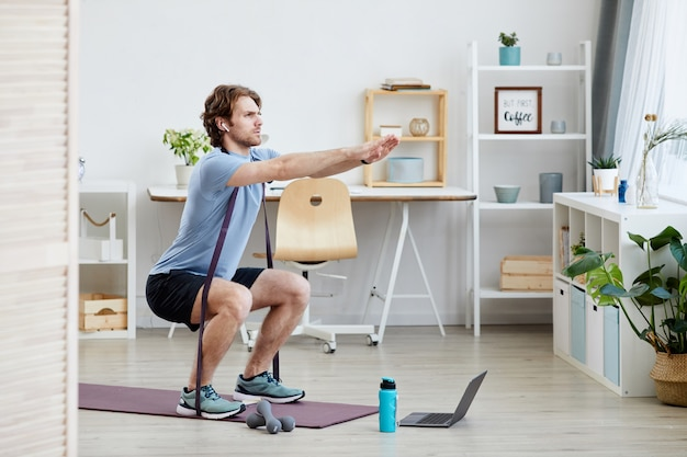 Giovane uomo in buona salute facendo esercizi sportivi nel soggiorno di casa