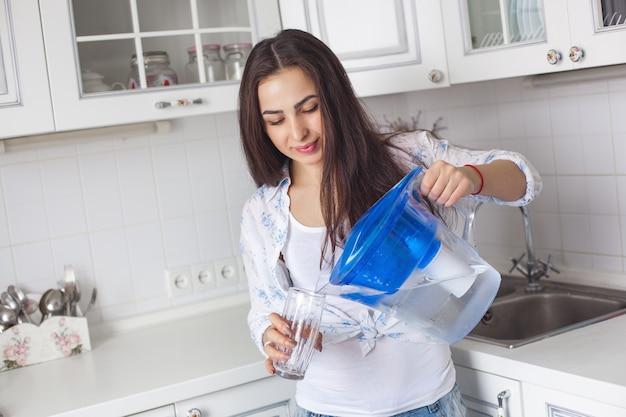 Giovane donna in buona salute che beve acqua filtrata sulla cucina