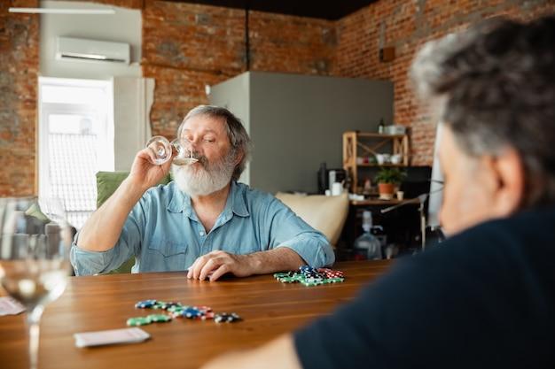 Giovane nel cuore. due amici maturi felici che giocano a carte e bevono vino. guarda felice, eccitato. uomini caucasici che giocano a casa. emozioni sincere, benessere, concetto di espressione facciale. buona vecchiaia.