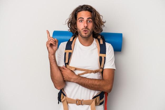 Giovane uomo caucasico escursionista isolato su sfondo grigio con qualche grande idea, concetto di creatività.