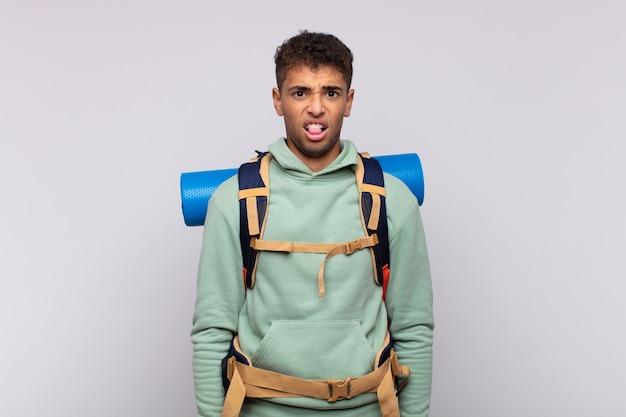 Giovane escursionista che si sente disgustato e irritato, sporge la lingua, non gli piace qualcosa di brutto e schifoso
