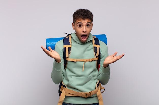 Giovane escursionista che si sente felice, eccitato, sorpreso o scioccato, sorridente e stupito per qualcosa di incredibile