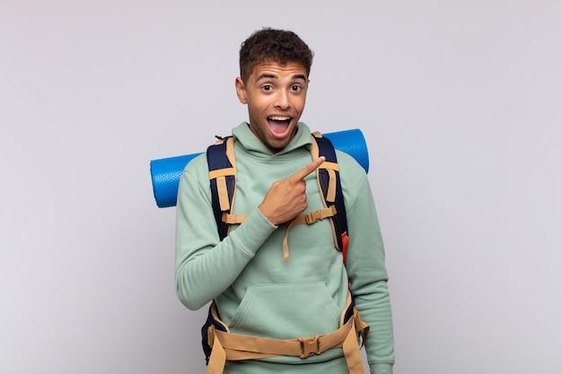 Uomo giovane escursionista che sembra eccitato e sorpreso che punta di lato e verso l'alto per copiare lo spazio