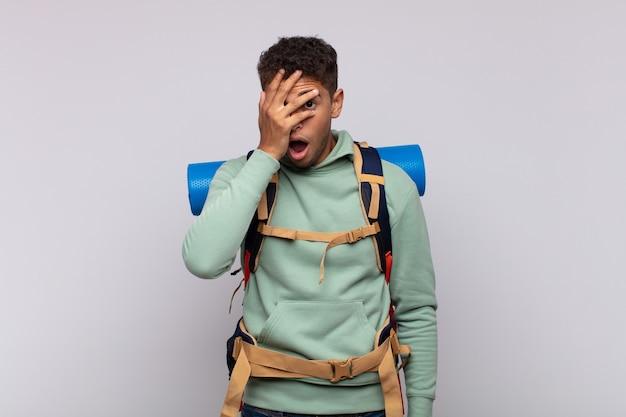 Giovane escursionista che sembra scioccato, spaventato o terrorizzato, coprendo il viso con la mano e sbirciando tra le dita