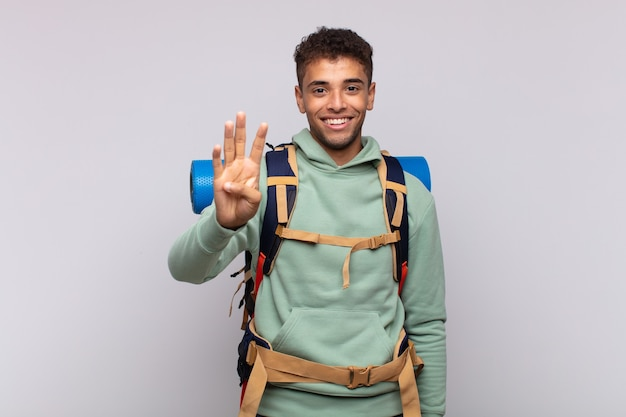 Uomo giovane escursionista sorridente e guardando amichevole, mostrando il numero quattro o quarto con la mano in avanti, conto alla rovescia