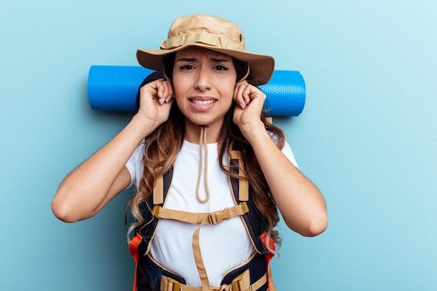 Donna di razza mista giovane escursionista isolata su sfondo blu che copre le orecchie con le mani.