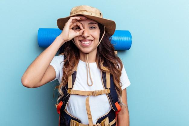 Donna di razza mista giovane escursionista isolata su sfondo blu eccitato mantenendo il gesto ok sull'occhio.