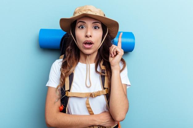 Donna di razza mista giovane escursionista isolata su sfondo blu con qualche grande idea, concetto di creatività.