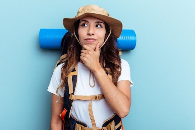 Donna di razza mista giovane escursionista isolata su sfondo blu guardando lateralmente con espressione dubbiosa e scettica.