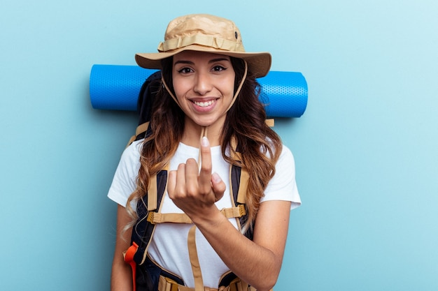 Giovane escursionista donna di razza mista isolata su sfondo blu che punta con il dito su di te come se invitasse ad avvicinarsi.