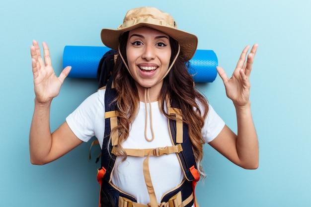 Giovane escursionista donna di razza mista isolata su sfondo blu che riceve una piacevole sorpresa, eccitata e alzando le mani.