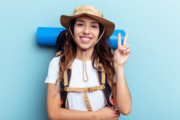 Giovane escursionista di razza mista donna isolata su sfondo blu che mostra il numero due con le dita.
