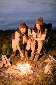 Giovani escursionisti seduti accanto al fuoco la sera sullo sfondo del fiume o del lago, rilassarsi e prendere un tè o un caffè con marshmallow fritti