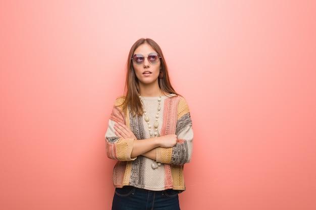 Giovane donna del hippie su fondo rosa stanco e annoiato