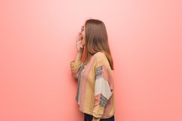 Giovane donna del hippie sulla parete rosa che bisbiglia sottotono di pettegolezzo