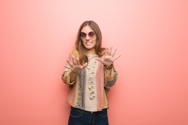 Giovane donna hippie che rifiuta qualcosa facendo un gesto di disgusto