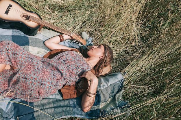 Giovane donna hippie con la chitarra sdraiato sull'erba