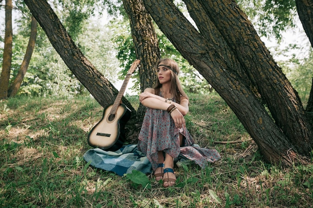 Giovane donna hippie con la chitarra seduta vicino a un albero nella foresta