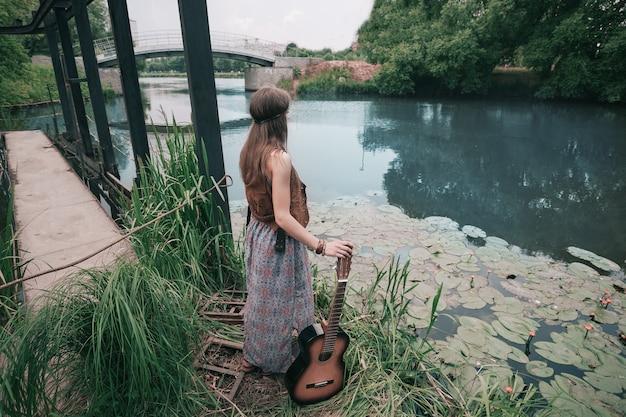 Giovane donna hippie con la chitarra in piedi vicino allo stagno